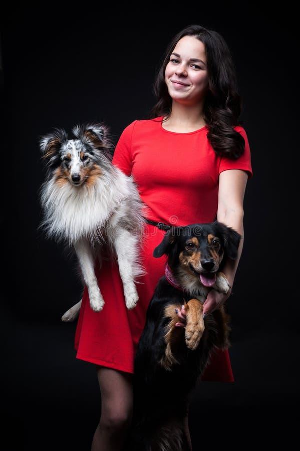 红色礼服的女孩有在黑背景的狗的 免版税库存图片