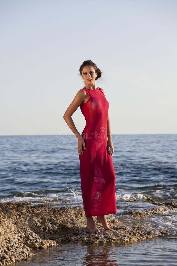 红色礼服的妇女在海滩 库存图片