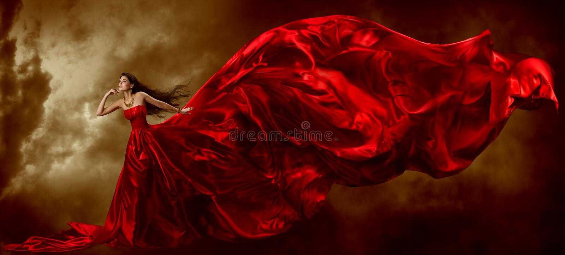 红色礼服的妇女有挥动的美丽的织品 免版税库存图片