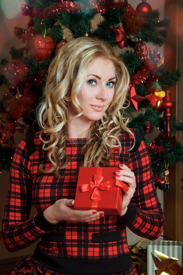 红色礼服的妇女有礼物箱子的在圣诞树下 库存照片