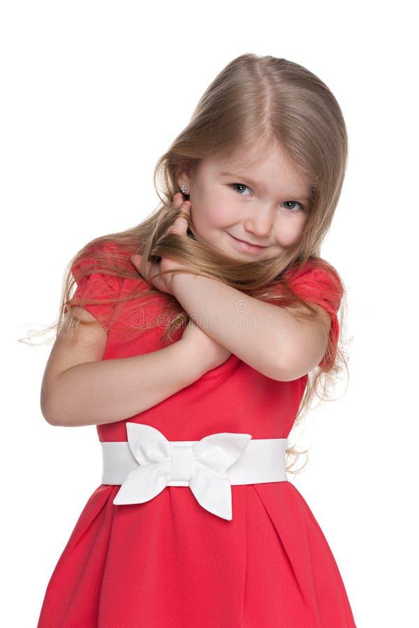 红色礼服的害羞的小女孩 库存图片