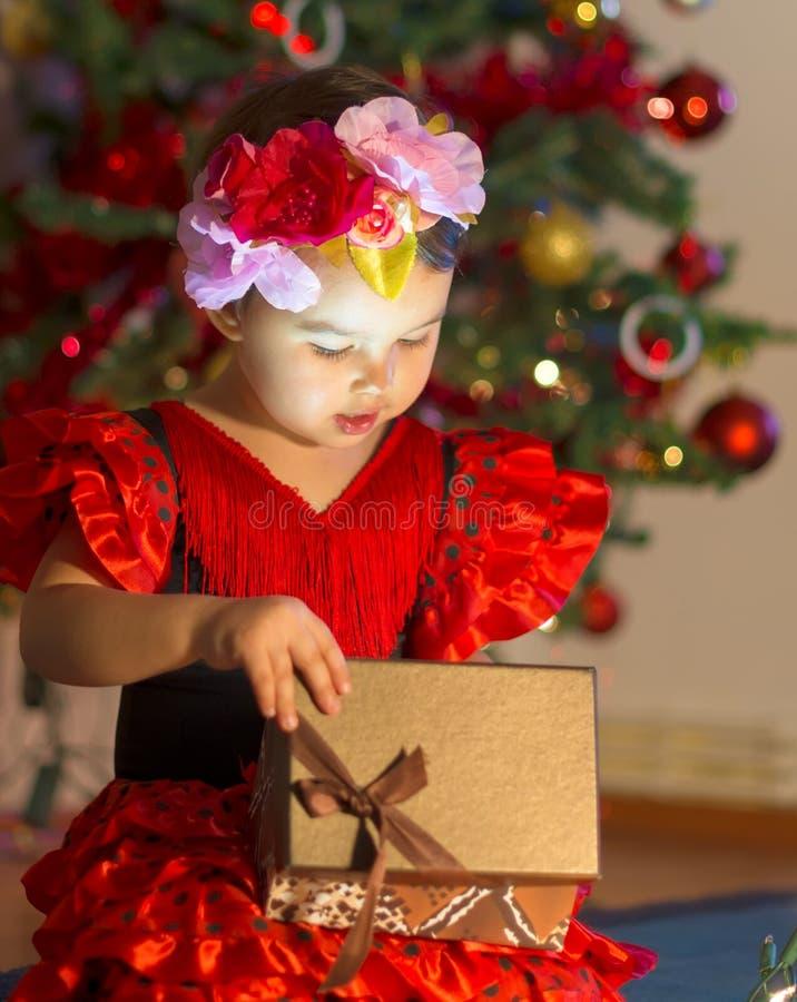 红色礼服的小女孩在圣诞树附近打开礼物 免版税库存图片