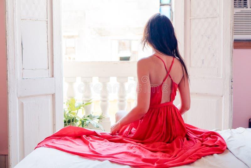 红色礼服的年轻可爱的妇女在公寓在哈瓦那 库存照片