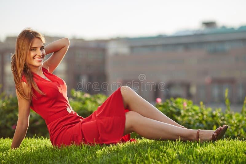 红色礼服的年轻美丽的微笑的妇女坐一个绿色草甸在城市公园 免版税库存照片