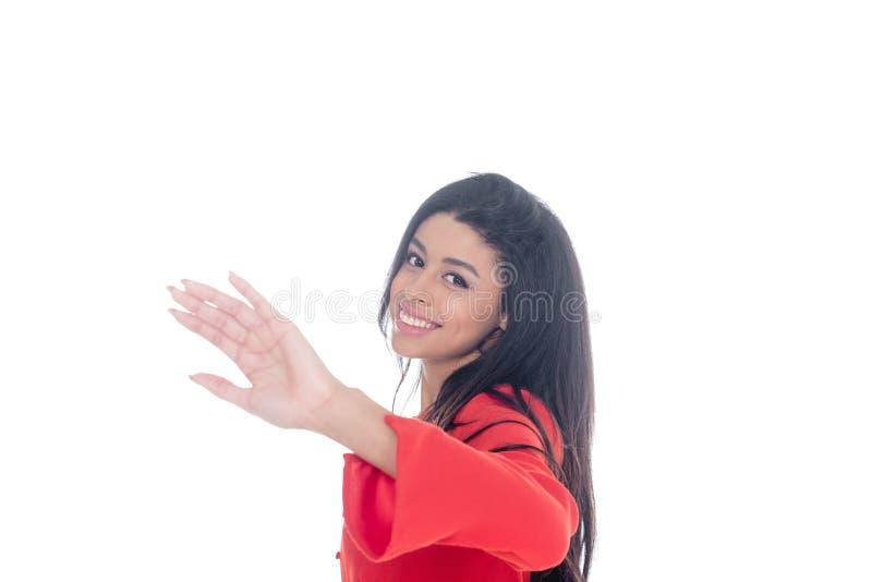 红色礼服的微笑的非裔美国人的女孩用手打手势和看照相机的被隔绝 免版税图库摄影