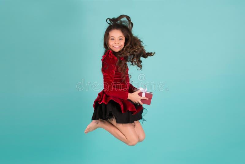 红色礼服的愉快的女孩有当前箱子的赤足跳 免版税库存照片