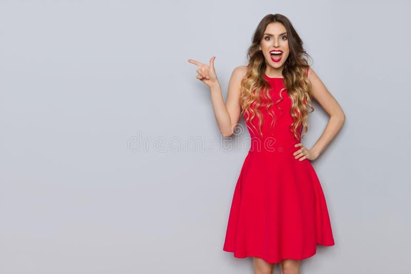 红色礼服的愉快的美丽的妇女指向并且呼喊 免版税库存照片