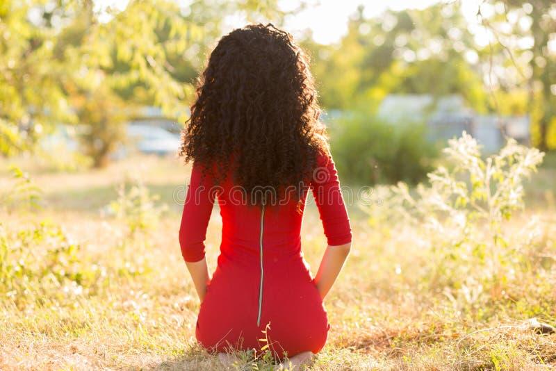 红色礼服的愉快的美丽的年轻女人在夏天公园放松 查出的黑色概念自由 库存照片