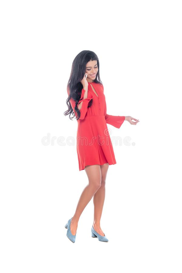 红色礼服的打手势微笑的非裔美国人的年轻女人谈话在智能手机和用手隔绝 库存照片