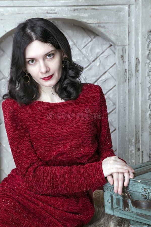 红色礼服的深色的少妇有组装的 免版税库存照片