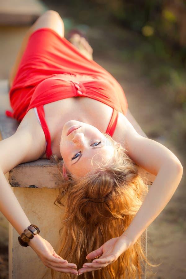 红色礼服的白肤金发的女孩在长凳说谎 库存照片