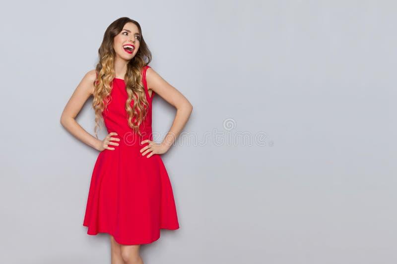 红色礼服的笑的妇女对灰色墙壁 库存图片