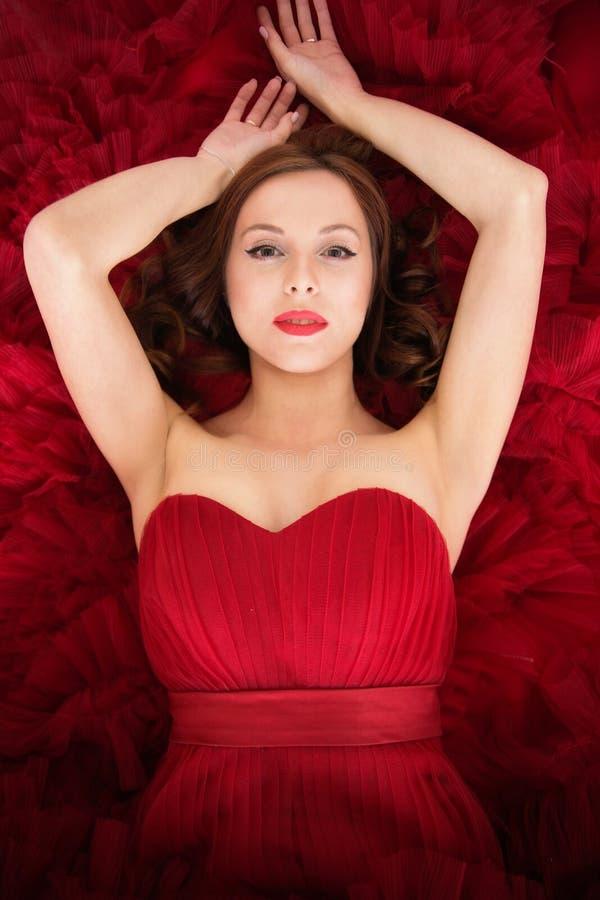 红色礼服的美丽的女孩有卷发的 免版税图库摄影