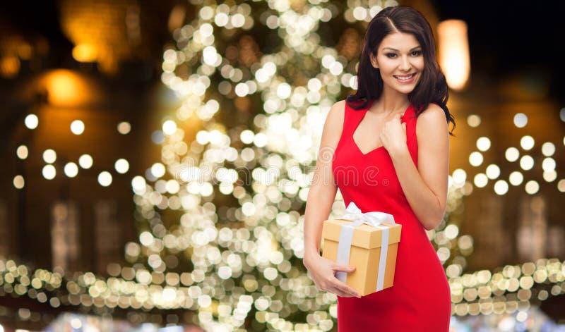 红色礼服的美丽的妇女有圣诞节礼物的 免版税库存照片