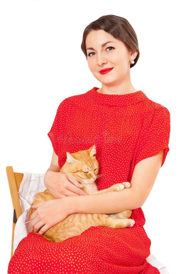 红色礼服的美丽的妇女有猫的 免版税库存图片