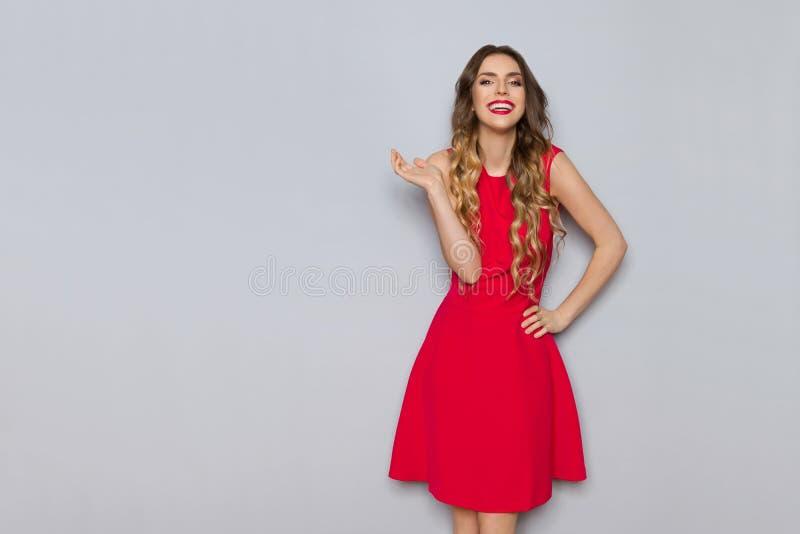 红色礼服的美丽的妇女笑并且打手势 库存图片