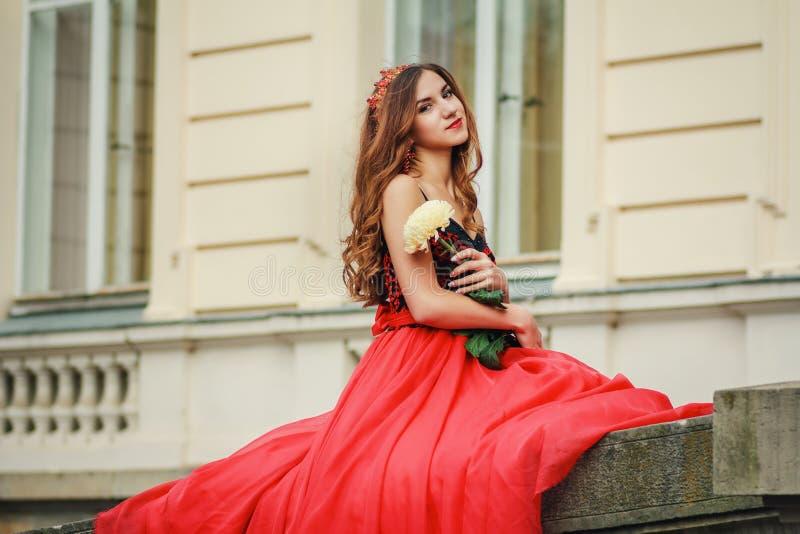 红色礼服的美丽的少妇拿着花 免版税库存图片