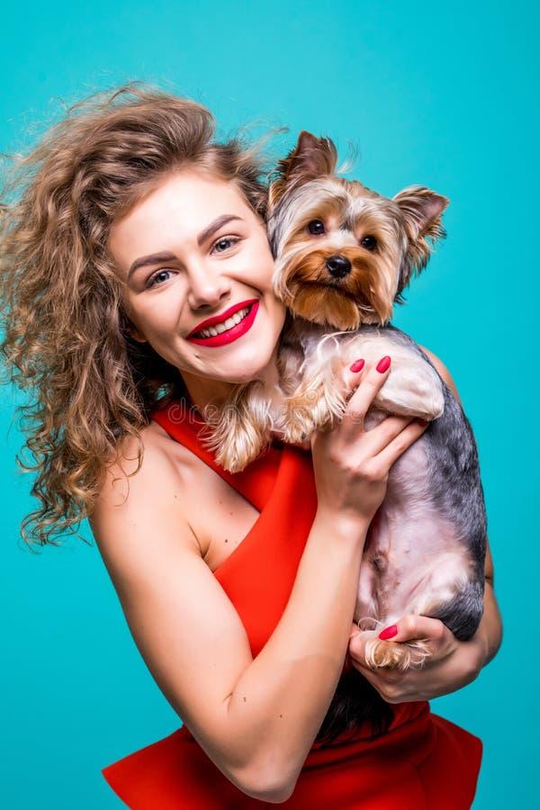 红色礼服的美丽的少妇有逗人喜爱的约克夏狗狗的,隔绝在绿色背景 免版税库存照片