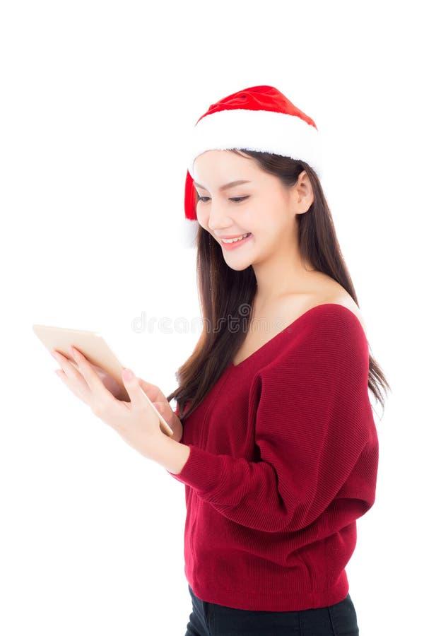 红色礼服的美丽的年轻亚裔妇女有拿着片剂的圣诞节帽子的 图库摄影