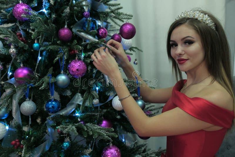 红色礼服的美丽的性感女孩装饰与气球的一棵圣诞树调查照相机 在妇女题材的设计  图库摄影