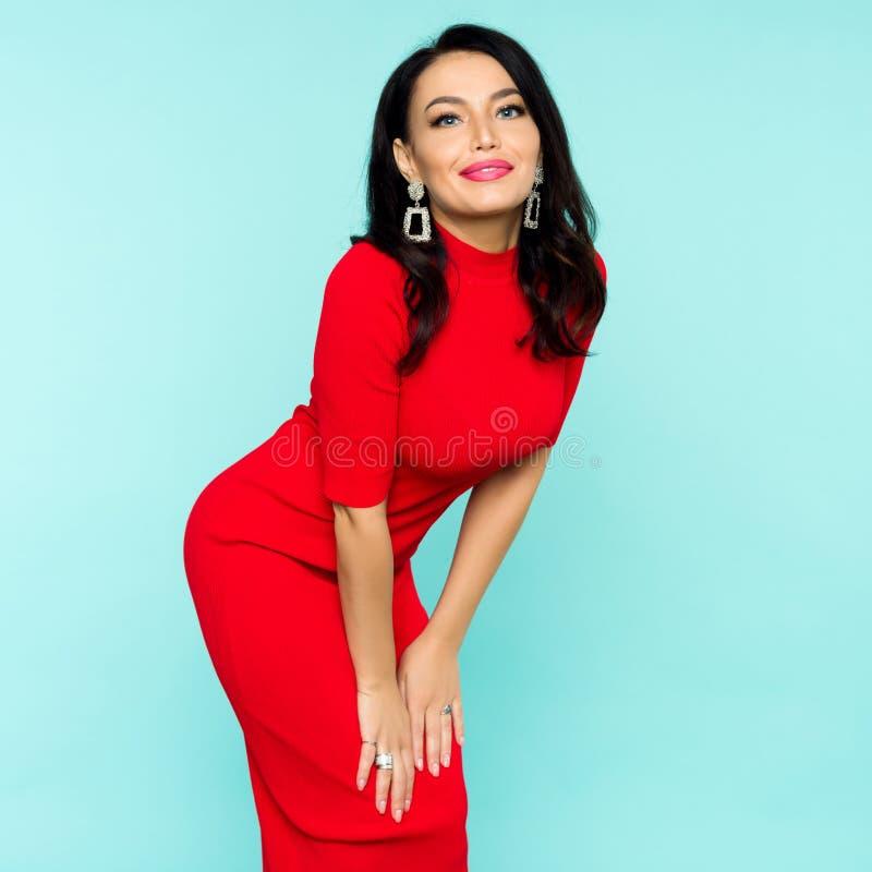 红色礼服的美丽的性感的深色的妇女在蓝色背景 图库摄影
