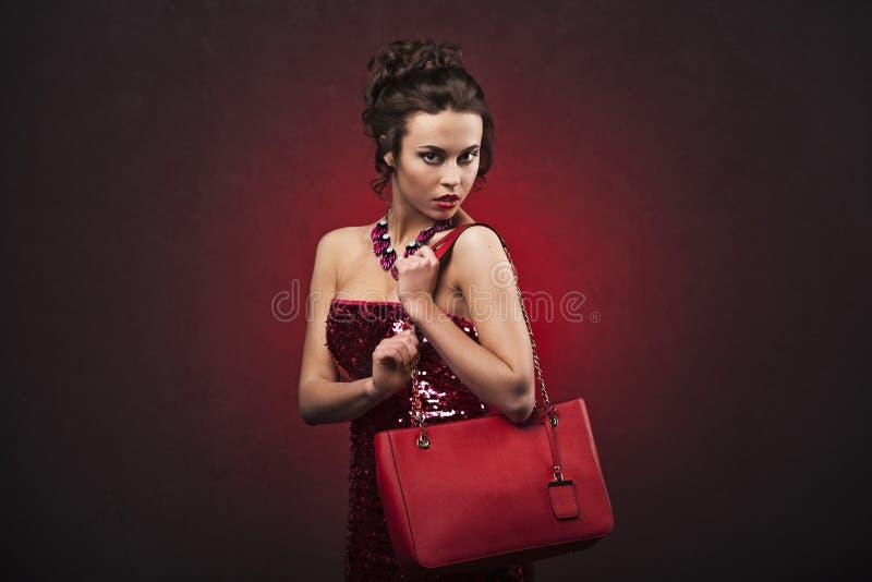 红色礼服的美丽的深色的妇女有专业构成和发型的与拿着红色提包的大项链 库存图片
