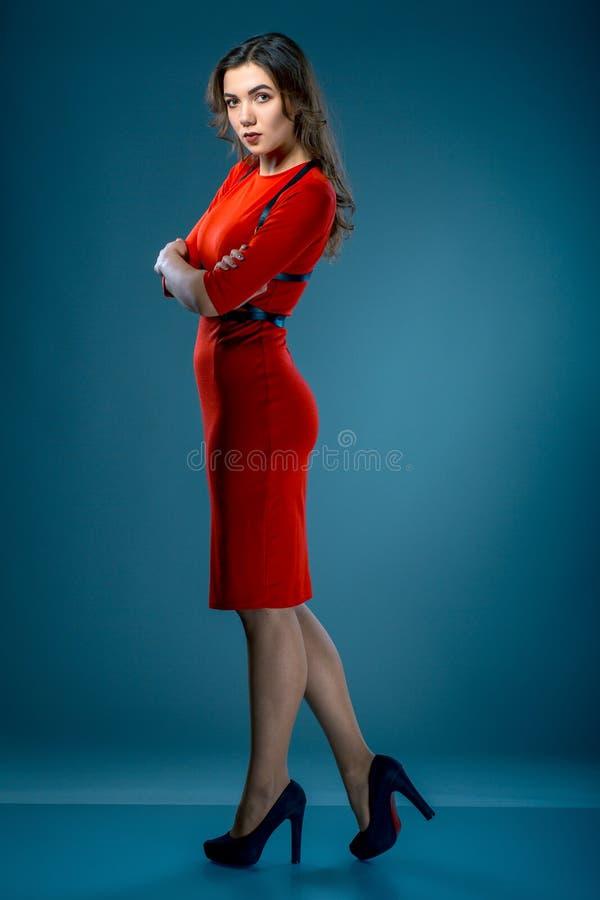 红色礼服的美丽的深色的妇女有传送带的在灰色蓝色背景的演播室摆在 免版税图库摄影