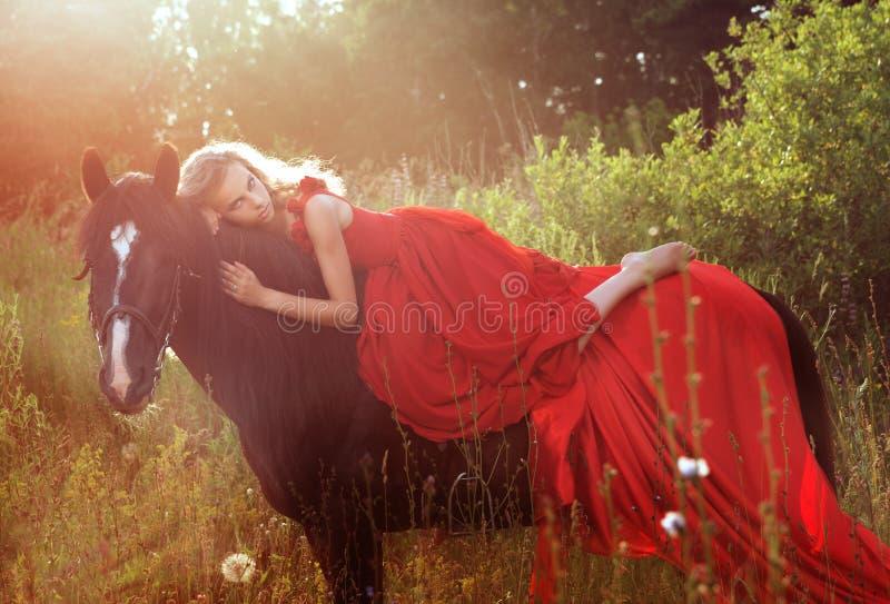 红色礼服的美丽的白肤金发的妇女在马 免版税库存图片