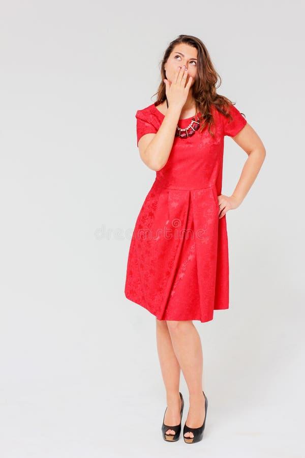红色礼服的美丽的迷人的深色的女孩关闭她的手嘴 图库摄影