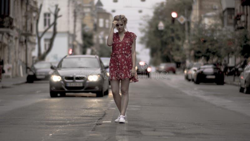 红色礼服的迷人的女孩为照相机摆在都市路背景 免版税库存照片