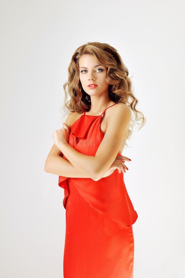 红色礼服的魅力女孩在白色 图库摄影