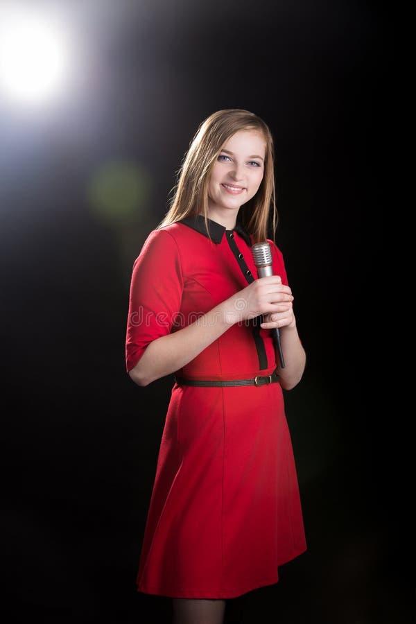 红色礼服的年轻女歌手 免版税图库摄影