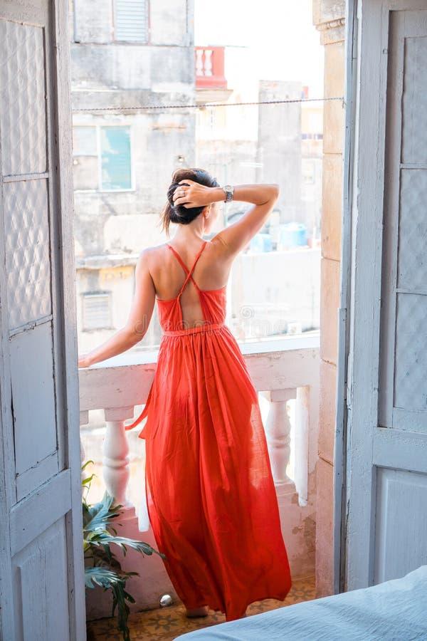 红色礼服的年轻美丽的妇女在公寓的老阳台在哈瓦那旧城,古巴 库存图片