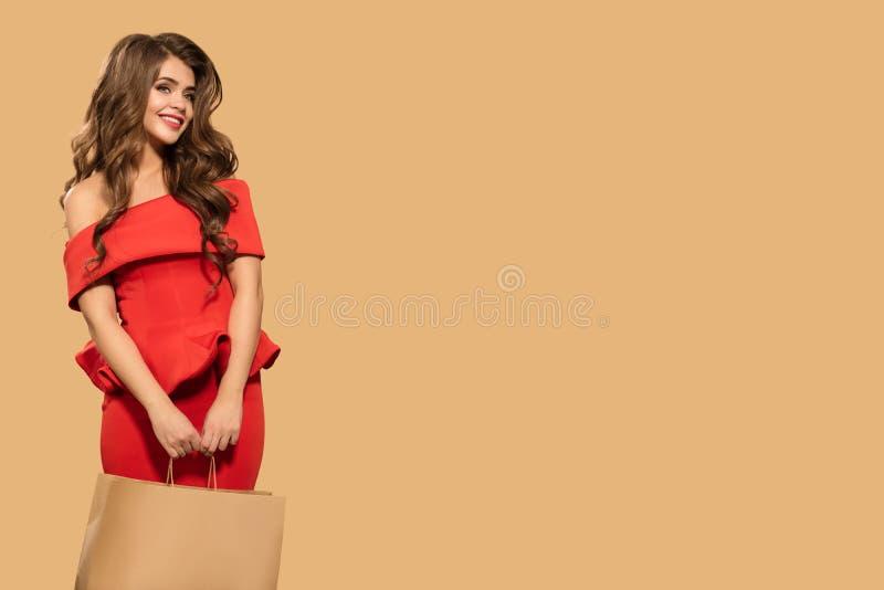 红色礼服藏品购物带来的美丽的愉快的妇女 免版税图库摄影