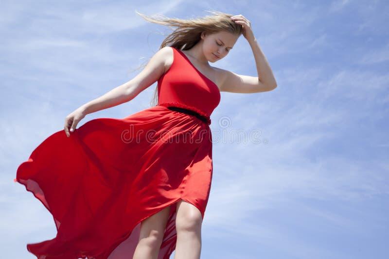 红色礼服身分的金发碧眼的女人反对天空蔚蓝 免版税库存照片