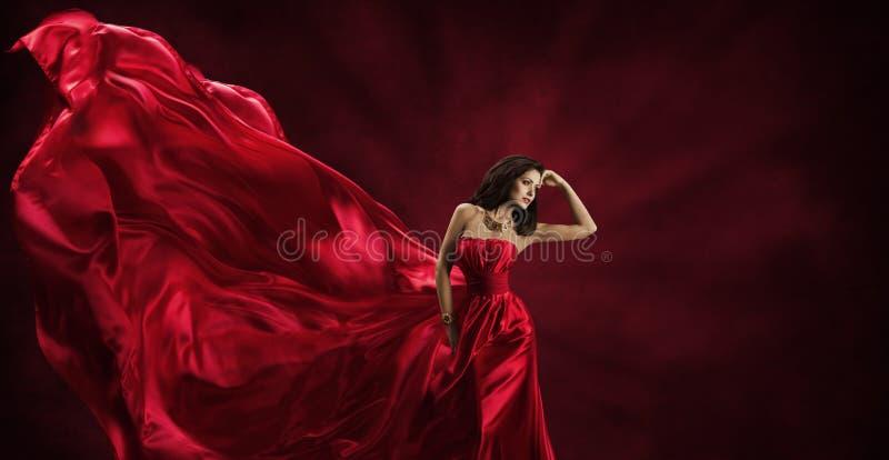 红色礼服,飞行时尚丝织物的妇女给模型穿衣 免版税库存照片