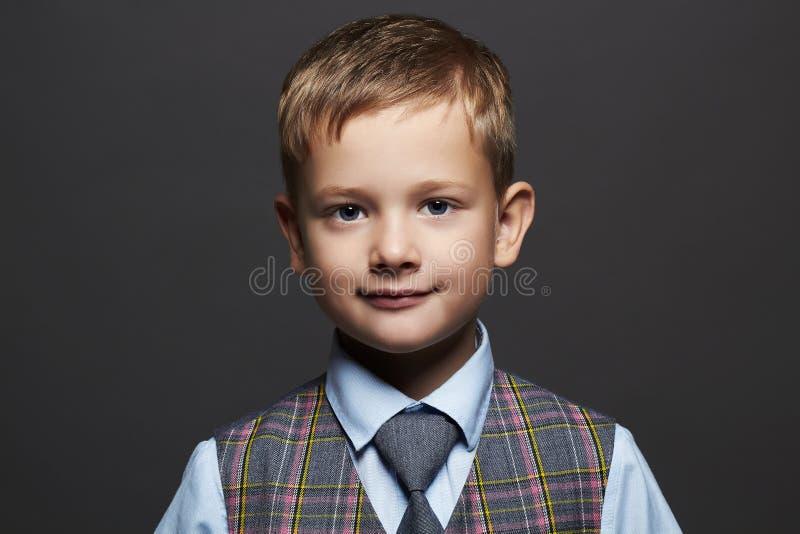 红色礼服 衣服和领带的微笑的滑稽的孩子 免版税库存图片