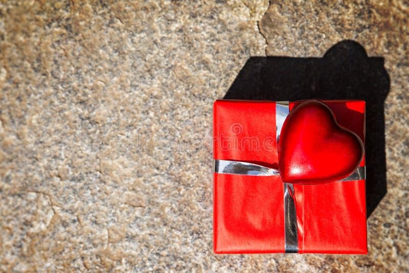 红色礼物和心脏在石背景 免版税库存照片