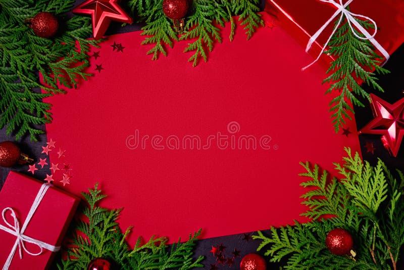 红色礼物盒、冷杉分支、五彩纸屑、纸文本的和玩具圣诞节框架在黑背景 平的位置 顶视图 复制 库存照片