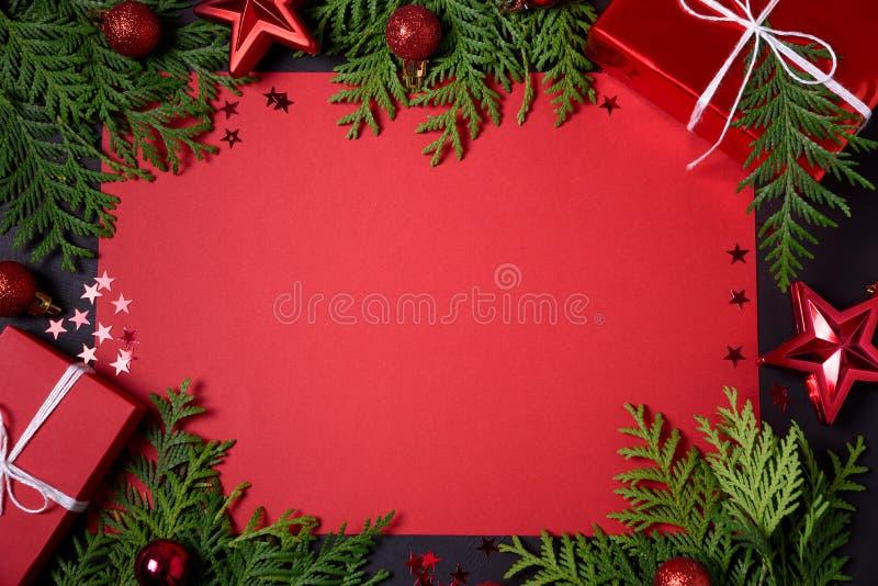 红色礼物盒、冷杉分支、五彩纸屑、纸文本的和玩具圣诞节框架在黑背景 平的位置 顶视图 复制s 库存照片