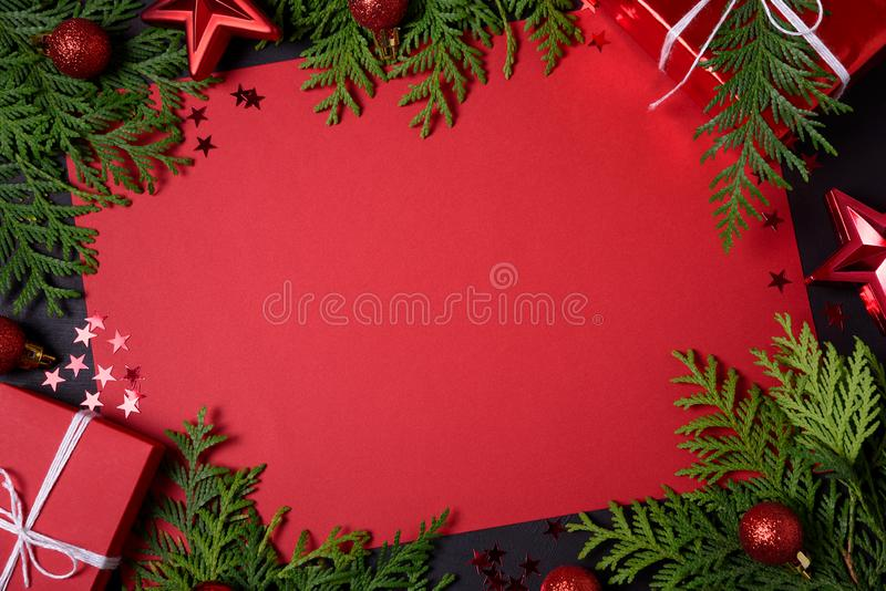 红色礼物盒、冷杉分支、五彩纸屑、纸文本的和玩具圣诞节框架在黑背景 平的位置 顶视图 复制s 免版税库存图片