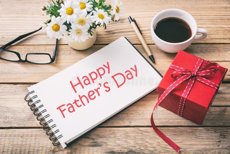红色礼物盒和愉快的父亲`天在笔记本,办公桌背景 免版税库存照片
