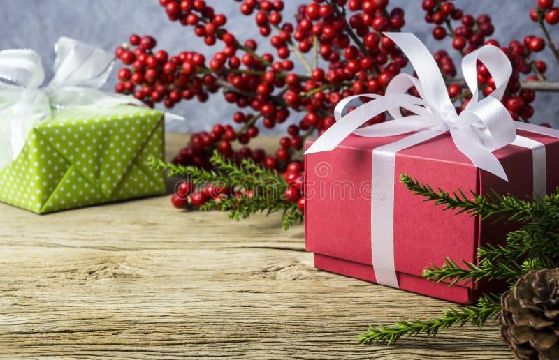 红色礼物盒和红色美洲冬青的圣诞节装饰 库存图片
