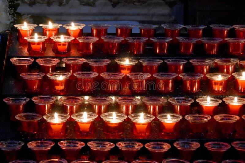 红色祷告蜡烛在教会里 免版税库存照片