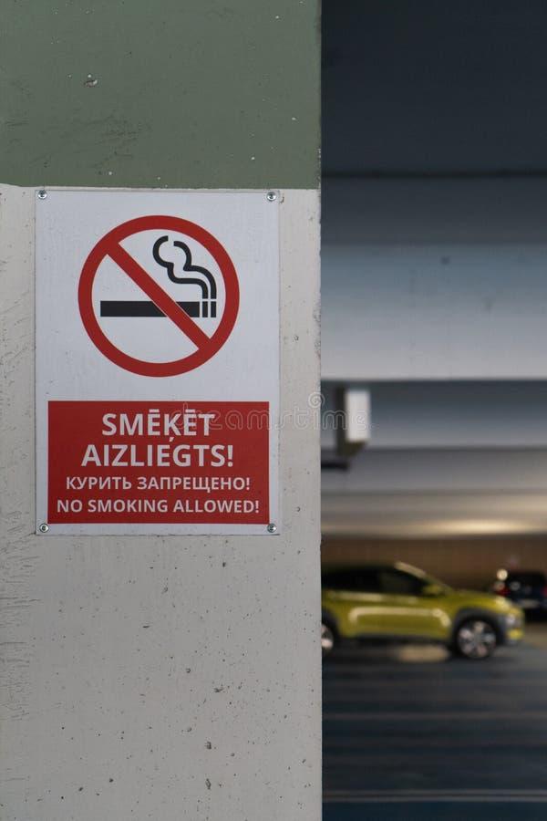 红色禁烟allower在地下停车处的三种语言签字与汽车可看见在背景中 图库摄影