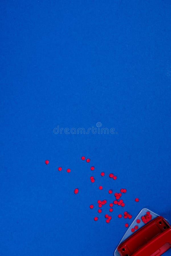 红色穿孔机和纸片断顶视图  免版税库存图片