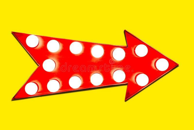 红色箭头塑造了与发光的电灯泡的葡萄酒五颜六色的被阐明的金属显示方向标在强烈的生动的黄色 免版税库存照片