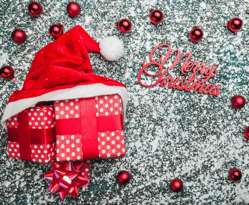 红色箱子和圣诞老人帽子在圣诞节背景 寒假题材,文本的空间 库存照片