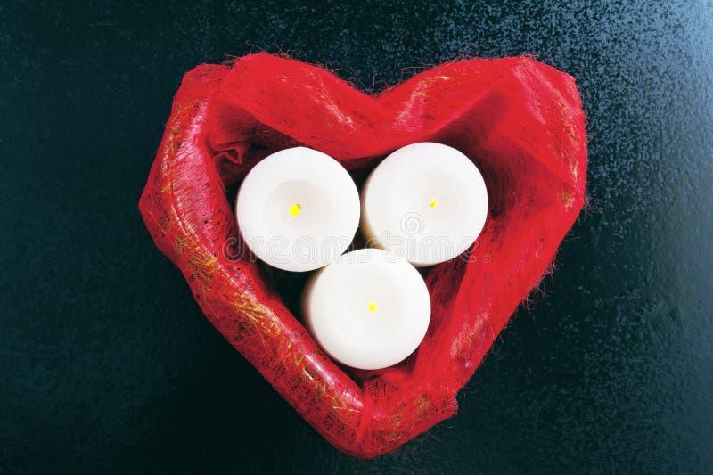 红色箱子在心脏形状和三个燃烧的白色蜡烛在蓝色背景