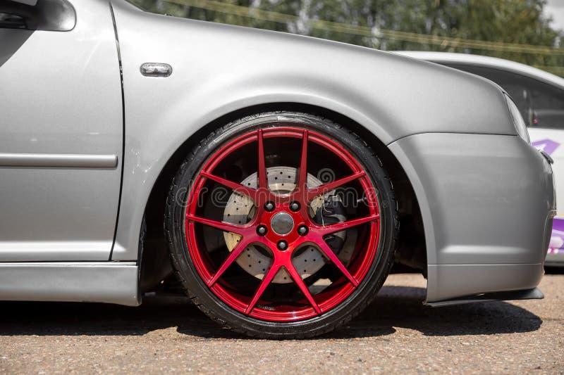 红色糖果在银色斜背式的汽车的色的轻合金轮子 免版税库存照片